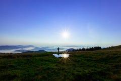 Haut dans les montagnes au-dessus des nuages un jeune homme recherche une connexion cellulaire tenant son téléphone haut photographie stock