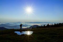 Haut dans les montagnes au-dessus des nuages un jeune homme recherche une connexion cellulaire tenant son téléphone haut photographie stock libre de droits