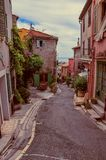 View of alley with houses in Haut-de-Cagnes, a pleasant village on top of a hill, near Nice. Haut-de-Cagnes, France - July 14, 2016. View of alley with houses Stock Photos