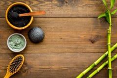 Haut Reinigung und Detox Bambusholzkohlenpulverkosmetik auf dunklem hölzernem Draufsichtraum des Hintergrundes für Text stockfoto