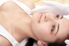 Haut und Körperpflege Nahaufnahme einer jungen Frau, die Badekur am Schönheits-Salon erhält Badekurort-Gesichts-Massage Gesichtss Lizenzfreie Stockbilder