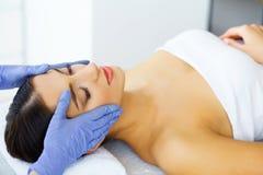 Haut und Sorgfalt Schöne junge Frau mit reiner und schöner Haut im Badekurort-Salon Massage für das Gesicht Lügen auf der Massage Stockfotografie