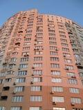 Haute construction rouge urbaine neuve, satellites, ciel bleu Photographie stock libre de droits