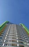 Haute construction urbaine neuve, couleur verte, ciel bleu Images libres de droits