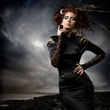 Haute couture. High fashion model in black dress, with long nails and creative hairstyling and makeup in stormy weather Stock Photography