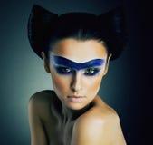 Haute Couturen. Fantasie. Noble Frau mit Blau gemalter Maske und moderner Frisur Stockbild