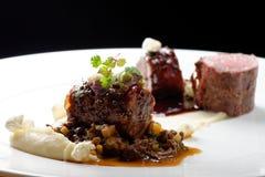 Haute cuisine, filetto di bue arrostito del vitello, coda del vitello con una salsa di porto, spugnole, lenticchie immagini stock
