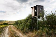 Haute peau de siège de chasseurs en bois sur le champ avec le ciel nuageux photographie stock libre de droits