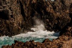 Haute roche brune avec une mer azurée orageuse images stock