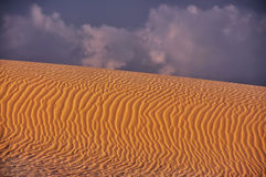 Hautes dunes dans le désert contre le ciel nuageux bleu Courbures faites de sable par le vent Photographie stock