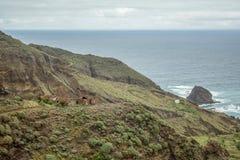 Hautes falaises raides de roche de lave dessus sur l'est de Ténérife Roches solitaires collant hors de l'eau Vieilles huttes aban photos libres de droits