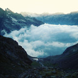 Hautes montagnes au-dessus des nuages - effet de vintage Vue de soirée Photographie stock