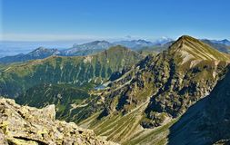 Hautes montagnes rocheuses sous le ciel bleu dans un jour ensoleillé images stock