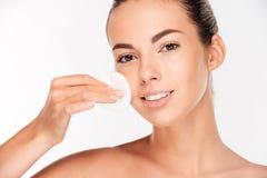 Hautpflegefrau, die Gesichtsmake-up mit Wattestäbchenauflage entfernt stockbild