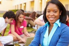 Hauts étudiants de Sitting Outdoors With de maître d'école sur le campus Photo stock