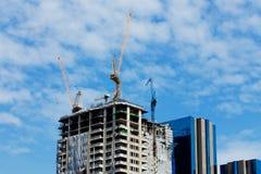 Hauts bâtiments en construction avec des grues à la soirée Photo stock