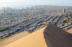 Hav bak stad bak sanddyn Fotografering för Bildbyråer