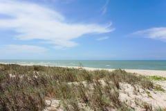 Hav, blå himmel, vitt moln och stranden med gräs på ett blåsigt D Royaltyfri Fotografi