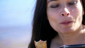 hav för strandvandringsledpir till stående av den härliga kvinnan, med långt mörkt hår, med apetite som äter pajen för körsbärsrö lager videofilmer