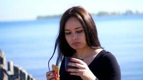 hav för strandvandringsledpir till stående av den härliga kvinnan, med långt mörkt hår, med apetite som äter pajen med te picknic arkivfilmer
