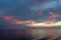 Hav i aftonen för solnedgång som är blandad med röda blått och guld s royaltyfri fotografi