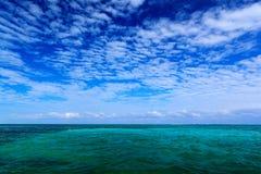 Hav i karibiskt med blå himmel och vitmolnet Vattenyttersida i havet Härligt landskap för morgonskymninghav Rosa färgen fördunkla arkivbilder