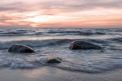 Hav och stenar på solnedgången Arkivfoto