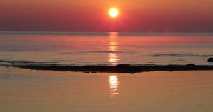 Hav på en solnedgångbakgrund och en reflexion av strålar i vattnet arkivfilmer