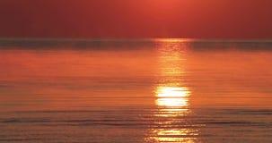 Hav på en solnedgångbakgrund och en reflexion av strålar i vattnet stock video