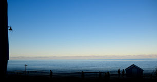 Hav på skymning, folk som promenerar stranden Royaltyfri Foto