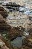 Hav, vågor, sand och stenar Arkivfoto