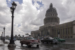 Havana Capitolio, Cuba. Old american cars passing by the Capitolio in Havana on a rainy day royalty free stock photos