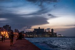 HAVANA, CUBA - OCTOBER 22, 2017: Havana Cityscape with Malecon Avenue and Caribbean Sea in Background. Blurry People Because of Lo. Havana Cityscape with Malecon Royalty Free Stock Images