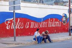 HAVANA, CUBA - APRIL 2, 2012: Cubaanse tieners die zitten dichtbij propag Stock Afbeeldingen
