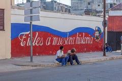 HAVANA, CUBA - APRIL 2, 2012:Cuban teenagers sitting near propaganda graffiti. HAVANA, CUBA - APRIL 2, 2012: Two cuban teenagers sitting near propaganda graffiti royalty free stock photos