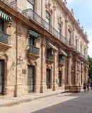 HAVANA, CUBA - APRIL 1, 2012: Tourists walk near Palacio De Los royalty free stock image