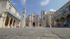 Low Angle Establishing Shot of Cathedral Plaza Square in Havana. 8864 HAVANA, CUBA - Circa July, 2017 - A low angle daytime establishing shot of tourists stock video footage