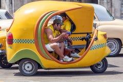 HAVANA, CUBA - 1º DE ABRIL DE 2012: Homem novo que tem o almoço no táxi amarelo Fotos de Stock Royalty Free