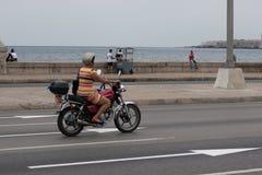 Havana, Cuba - 13 de abril de 2017: Uma mulher conduz uma motocicleta ao longo do Malecon em Havana fotos de stock royalty free