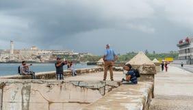 HAVANA, CUBA - 21 DE OUTUBRO DE 2017: Avenida de Malecon em Havana, Cuba Povos que levantam na frente do mar das caraíbas imagens de stock