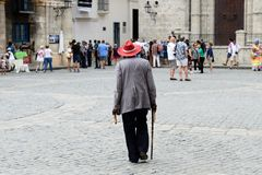 Retro walk in Havana. HAVANA, CUBA - 06 DECEMBER 2016: The resident of Havana is walking before the Cathedral in the hat and with the cigar in hand, amongst Royalty Free Stock Photo