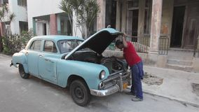 Havana, Cuba, fixing old American car. Cuban in Havana fixing old American car