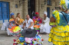 HAVANA, CUBA - JANUARY 04, 2018: Cubans in national clothes take. Pictures with tourists on the square in Havana, Cuba Stock Image