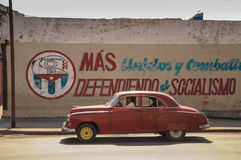 Havana, CUBA - JANUARY 20, 2013: Old classic American car drive. On street of Havana,CUBA on front of political slogan on wall. Old American cars are iconic Royalty Free Stock Photography