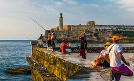 Havana, Cuba. June 2018. El Malecon of Havana: cuban people fishing at sunset. Havana, Cuba. June 2018. El Malecon of Havana: cuban people fishing and relaxing Stock Images
