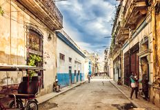 Free Havana, Cuba - March, 29th 2012: Typical Scene Of Old Havana Narrow Street And Old Building, Local People And Tourists On Destroye Stock Image - 99906411