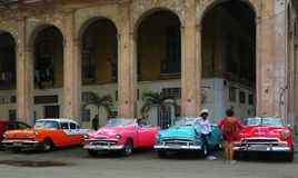 Multi colored taxis waiting for tourists in central Havana. Havana, Cuba - March 11, 2018: American classic cars painted in vivid colors parked in central Havana royalty free stock images