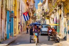 Urban scene with cuban flag and decaying buildings in Old Havana. HAVANA,CUBA - MARCH 16,2018 : Urban scene with cuban flag and colorful decaying buildings in royalty free stock photo
