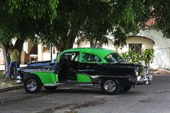 Black and green classic car used as a taxi. Havana, Cuba - March 12, 2018: A well-mantained black and green classic car, used as a taxi, parked under a tree Stock Photos