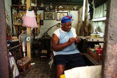 Havana, Cuba, May 31, 2016: An old woman stringing beads as business stock photography